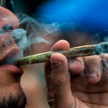 Мужчина курит косяк с коноплей