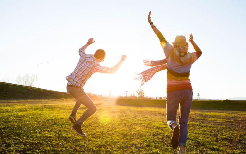 Счастливые люди скачут на солнце