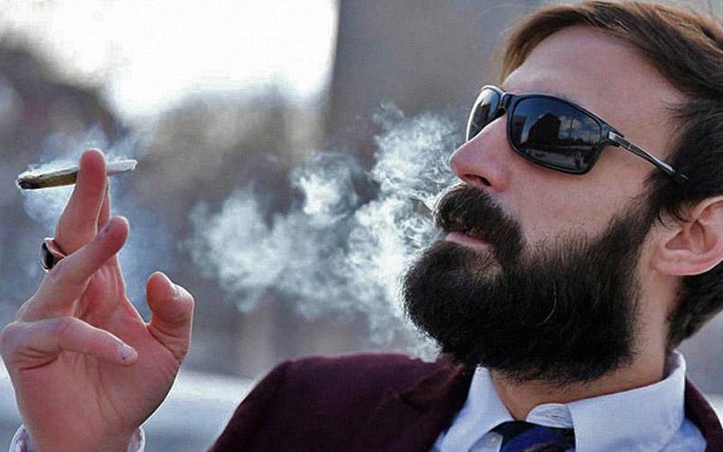 Мужчина с бородой курит марихуану