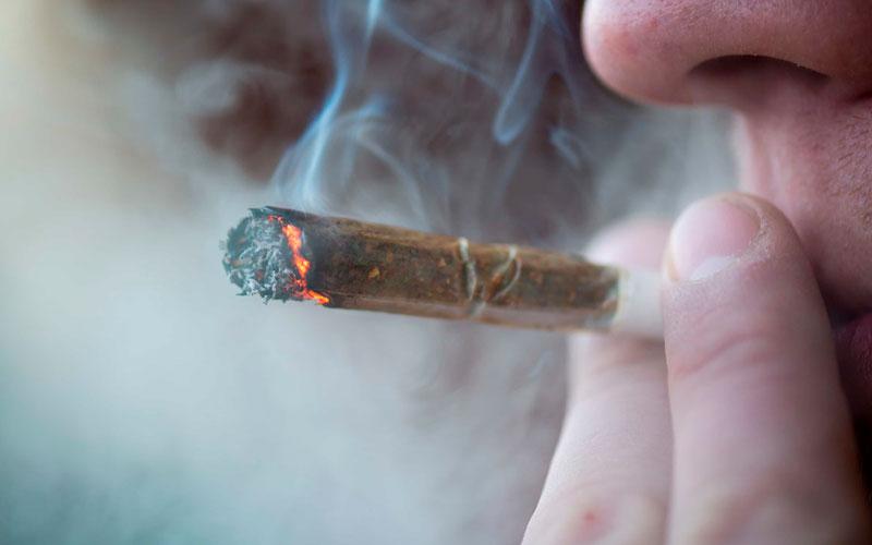 мужчина курит сигарету с коноплей